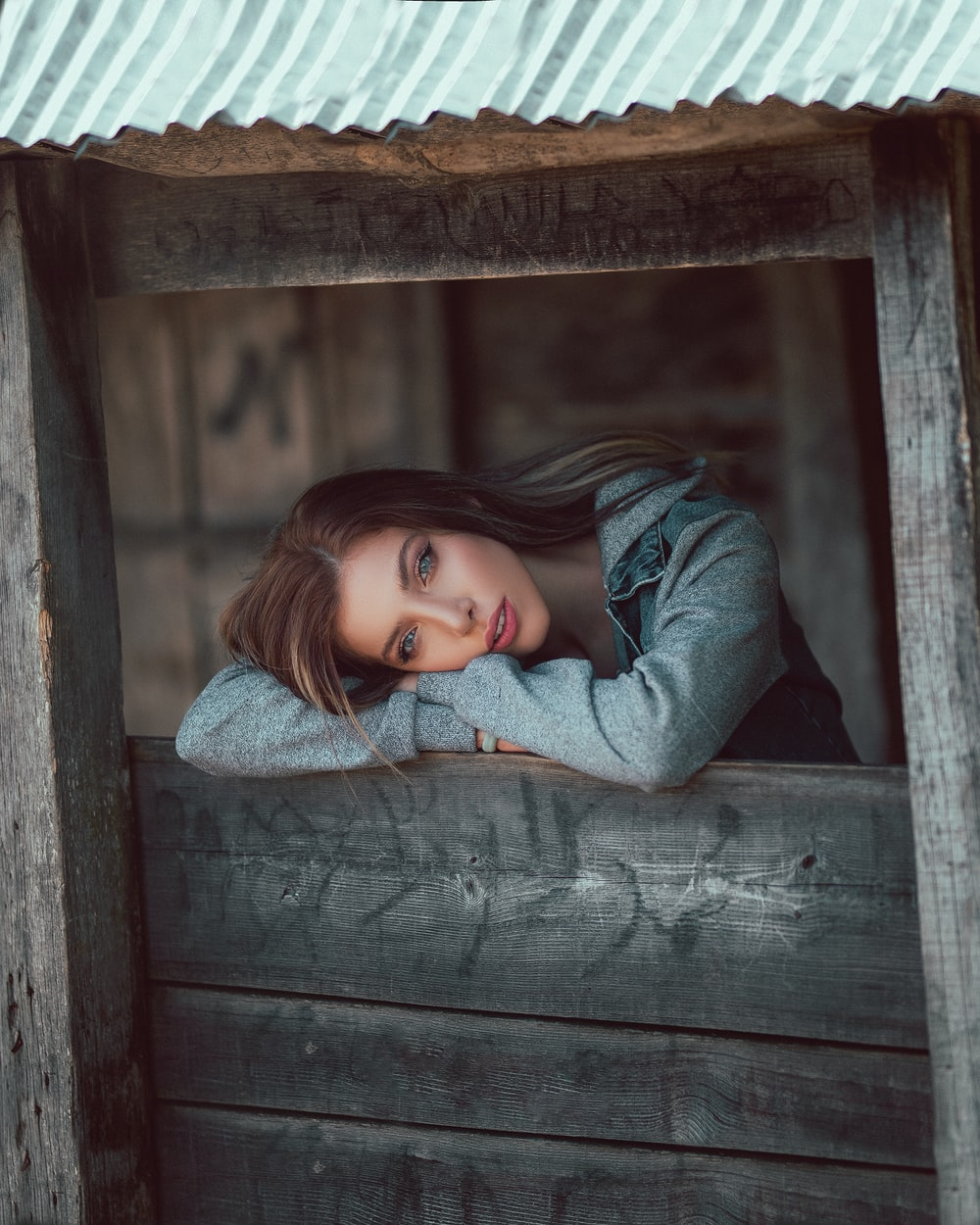 woman leaning forward on wooden window sill