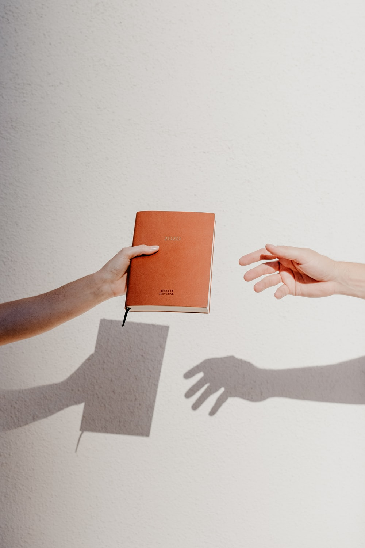 person holding orange book