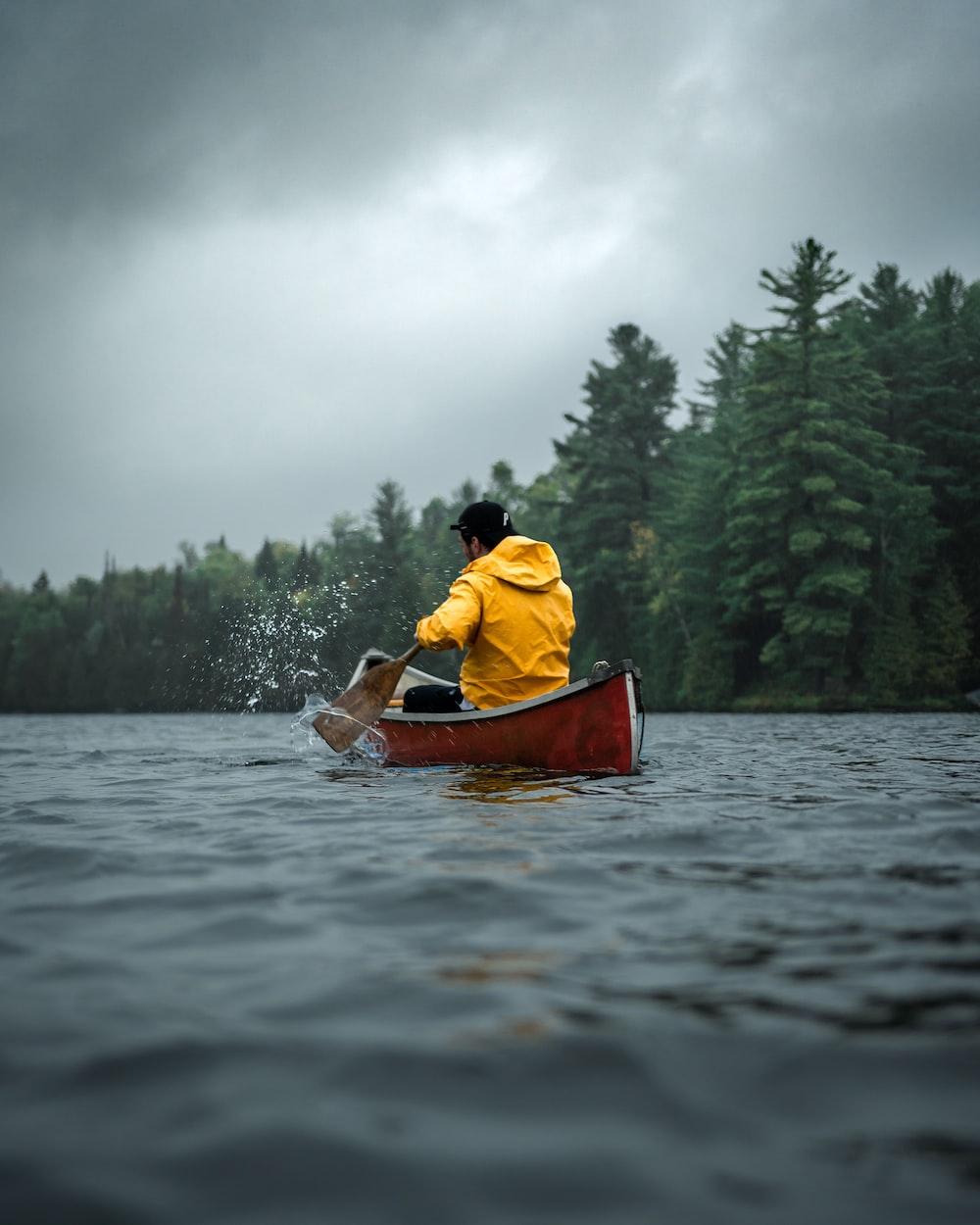 man wearing orange hoodie riding red canoe on lake