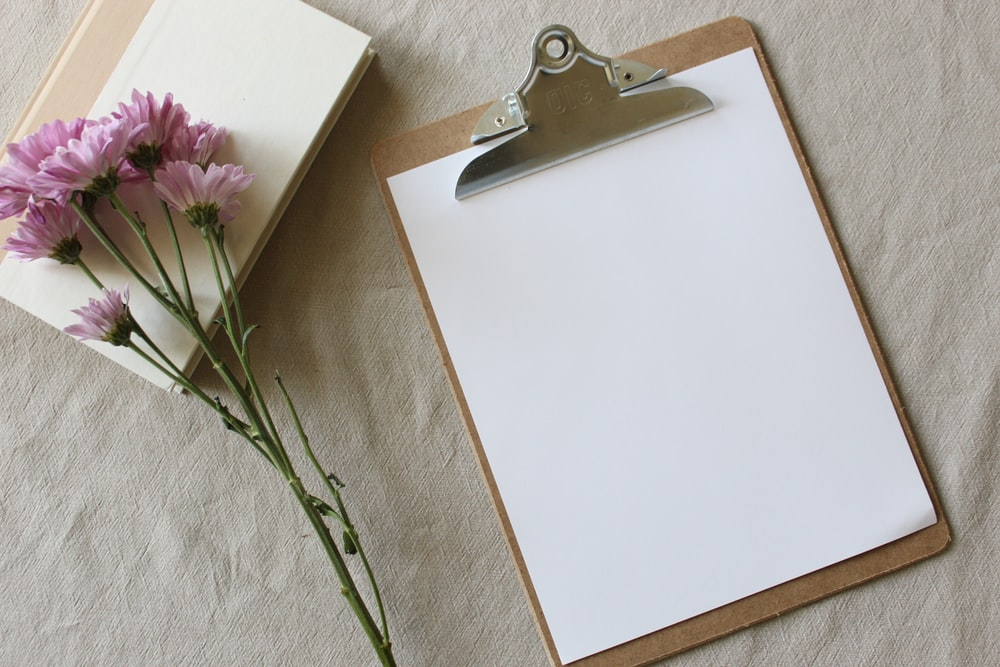 purple flower on white box and brown clipboard