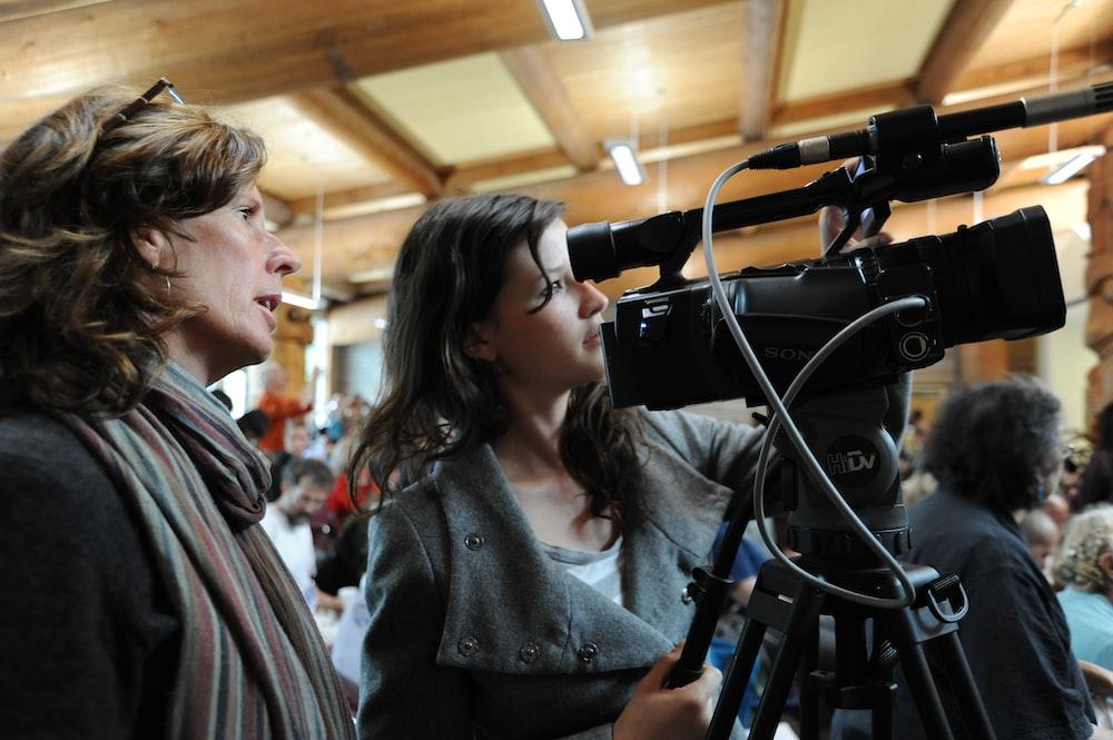 two women standing beside camera