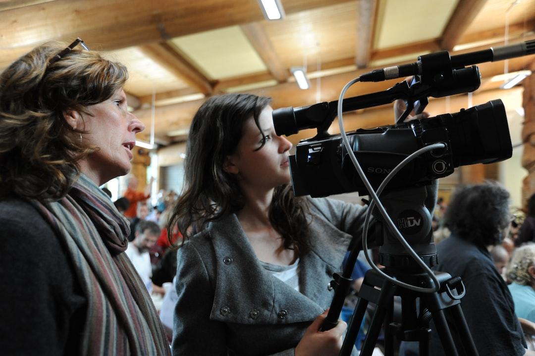Women recording video, of Tibetan Buddhist lama Dilgo Khyentse Yangsi Rinpoche, Lotus Speech, First Nations Longhouse, University of British Columbia, Vancouver, BC, Canada