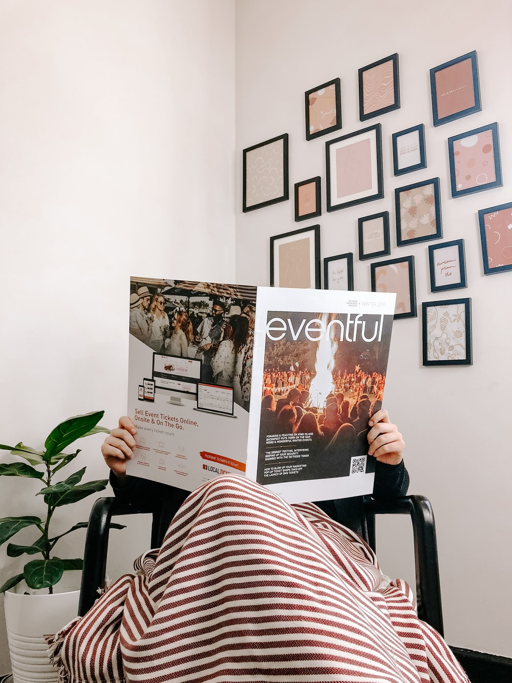 person sitting on armchair reading magazine