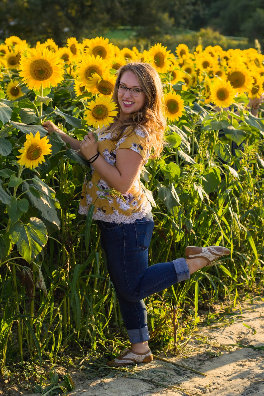 woman smiling and standing on one leg beside sunflowers