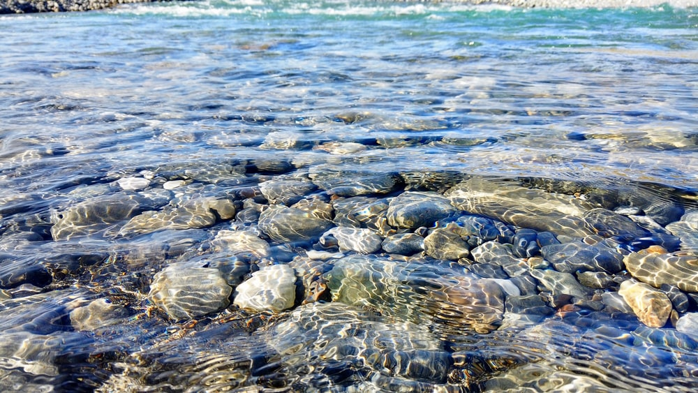 stones under clear body of water