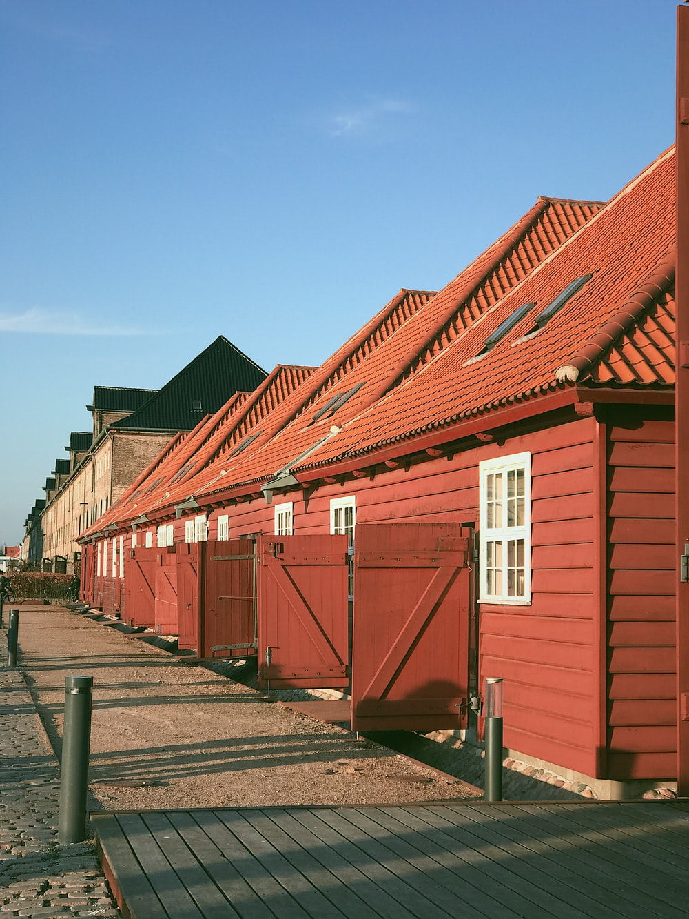 red wooden cottages under a calm blue sky