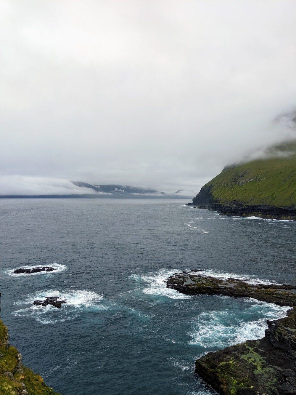 seashore rocks during cloudy day