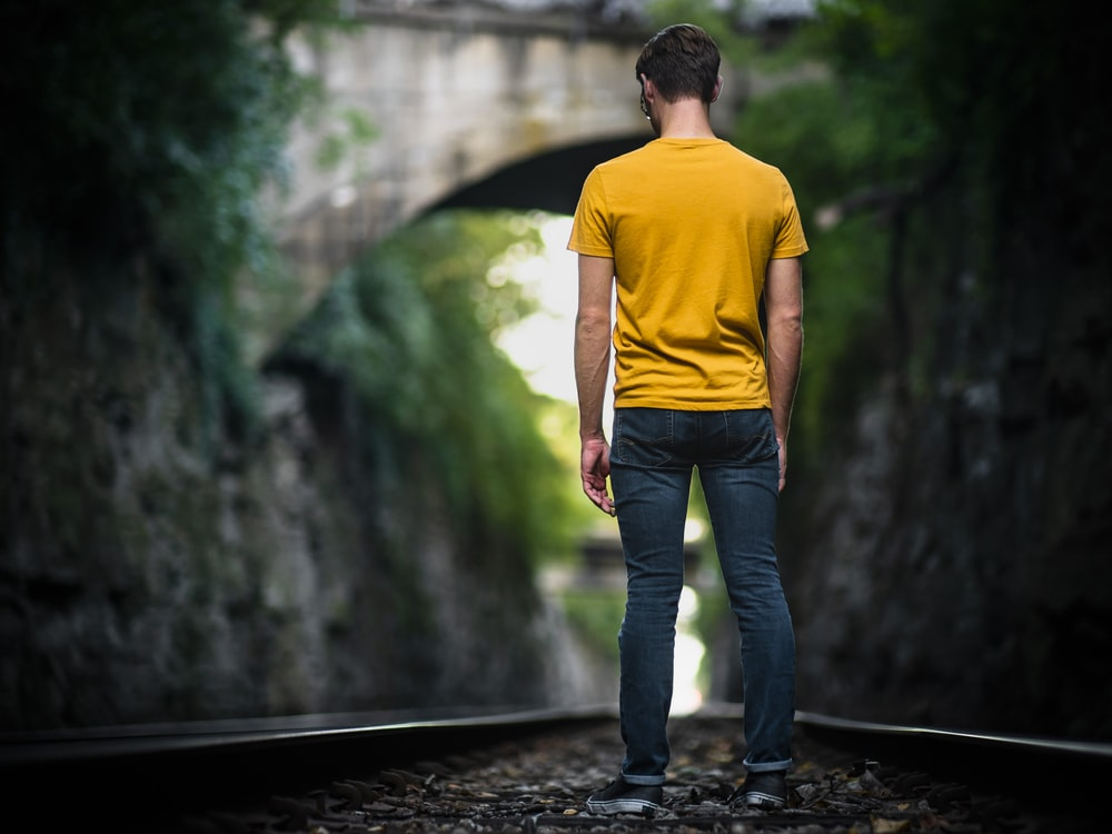 man standing in the middle of train track