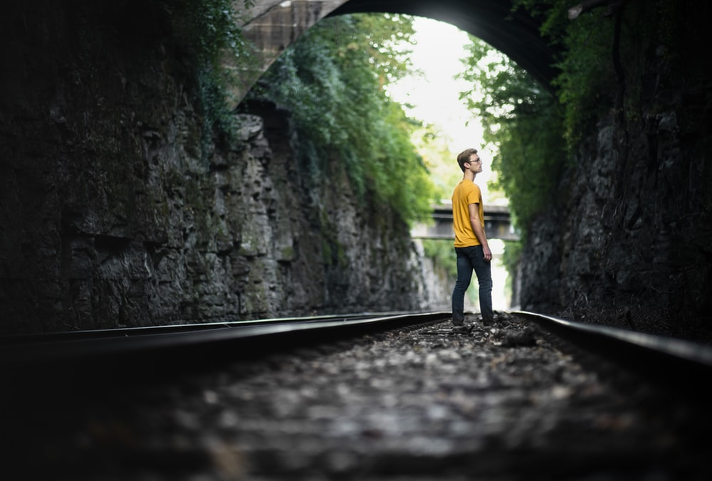 man standing on railway