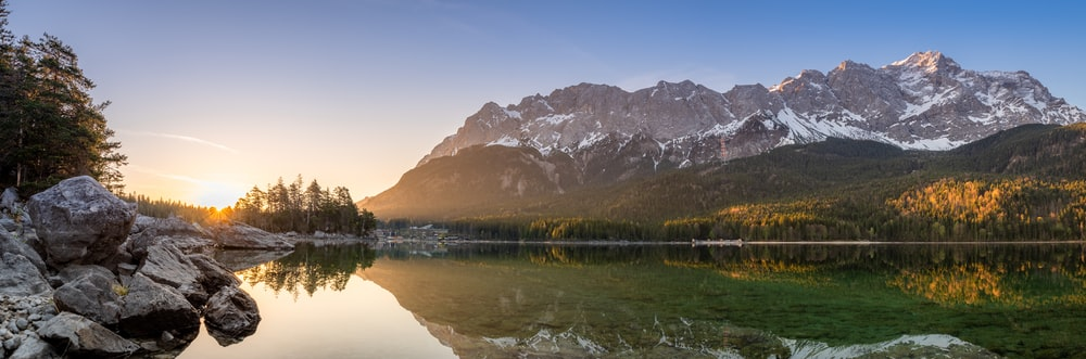 lake surrounded with tall and green trees viewing mountain during sunrise