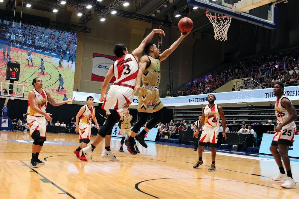 men playing basketball inside building