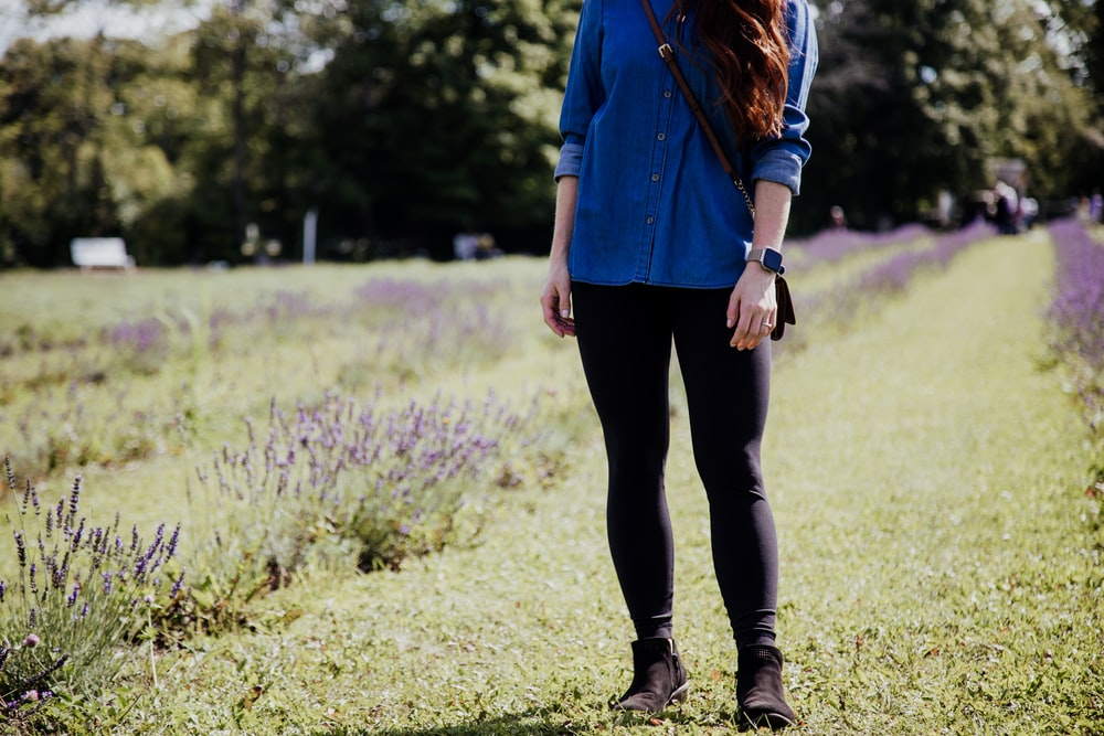 woman wearing blue blouse and black leggings standing on grass