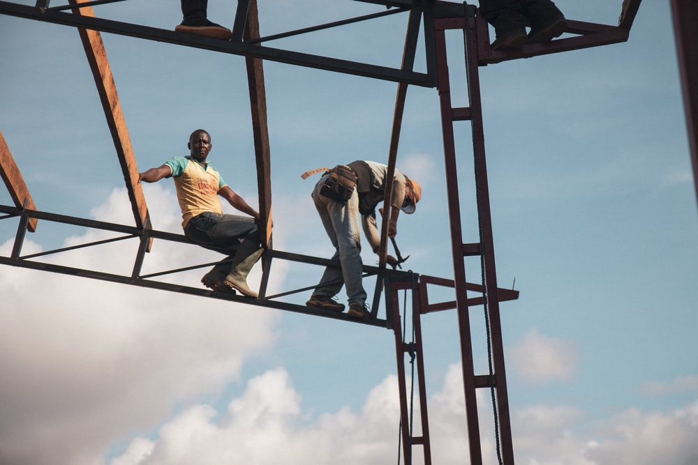 low-angle photography of two men on metal frame tower