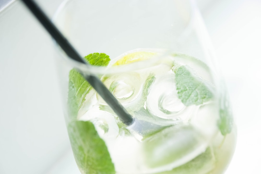 mojito in clear drinking glass with black straw
