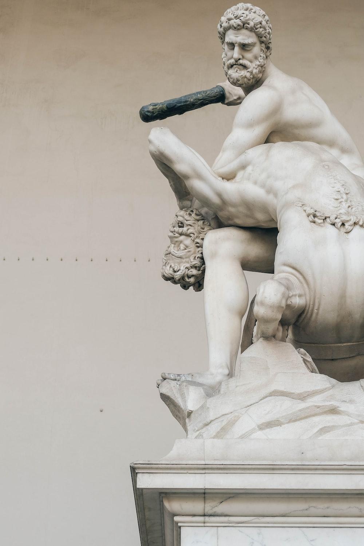 man sitting on man statue