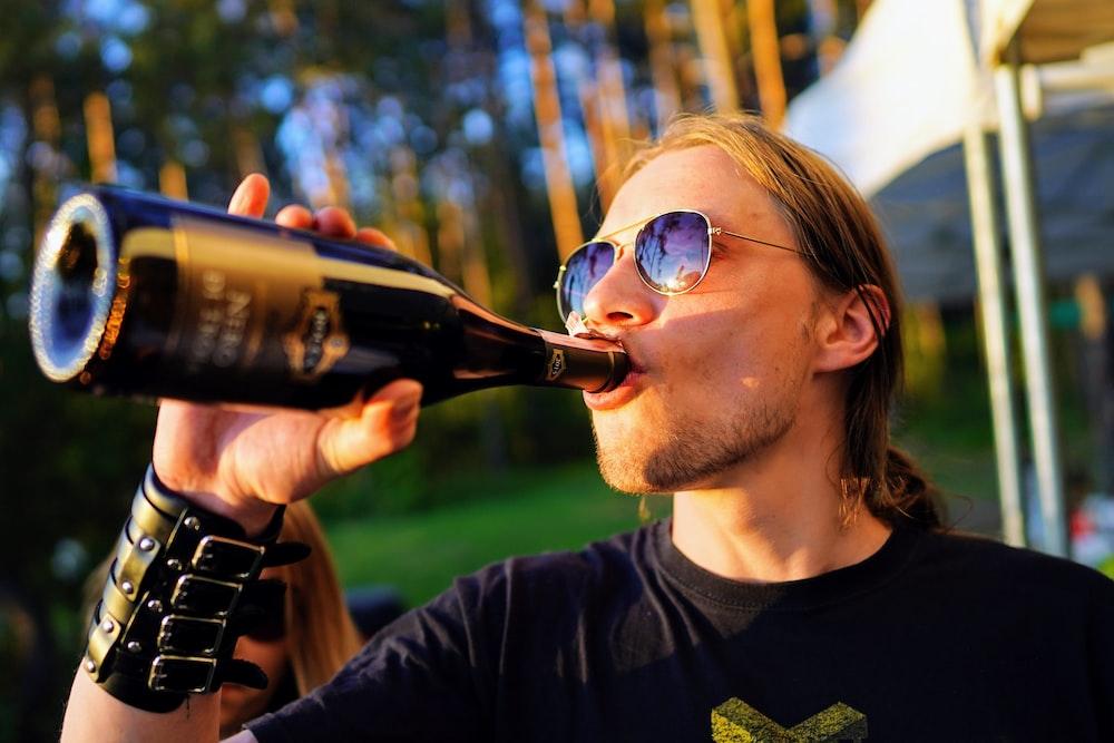 man wearing black crew-neck t-shirt drinking
