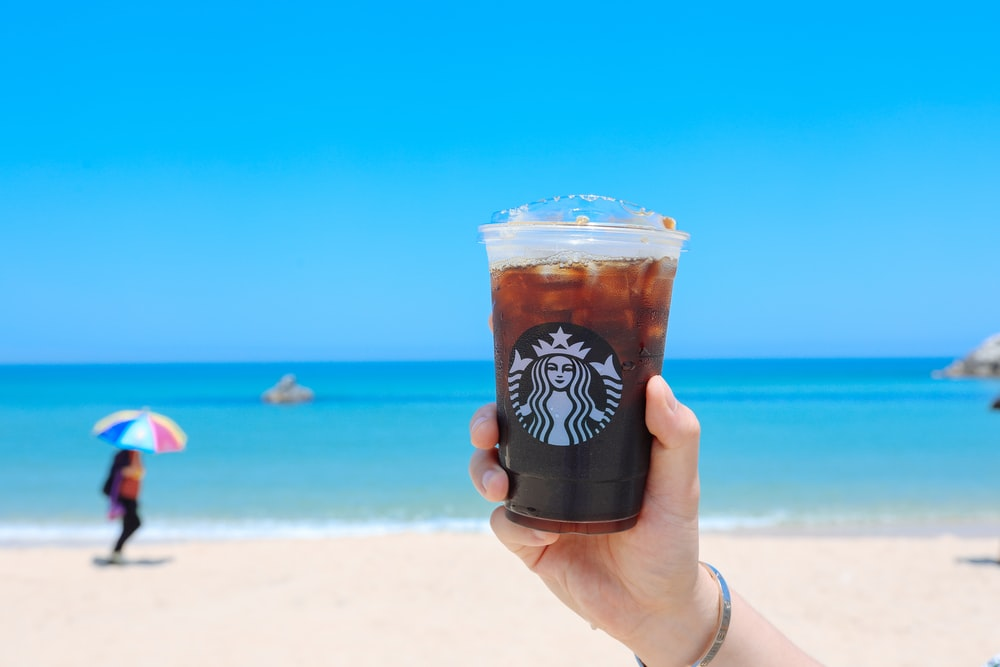 person holding clear StarBucks disposable cup