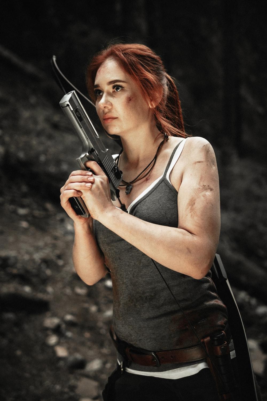 woman wearing gray spaghetti strap blouse holding gray rifle