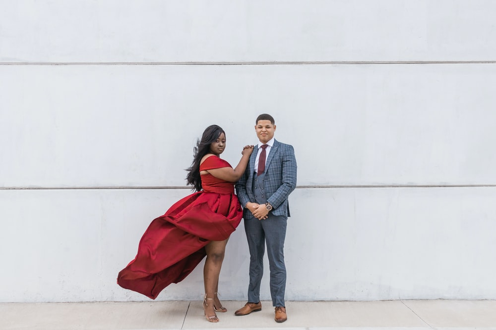 woman wearing red dress and man wearing gray suit jacket and pants