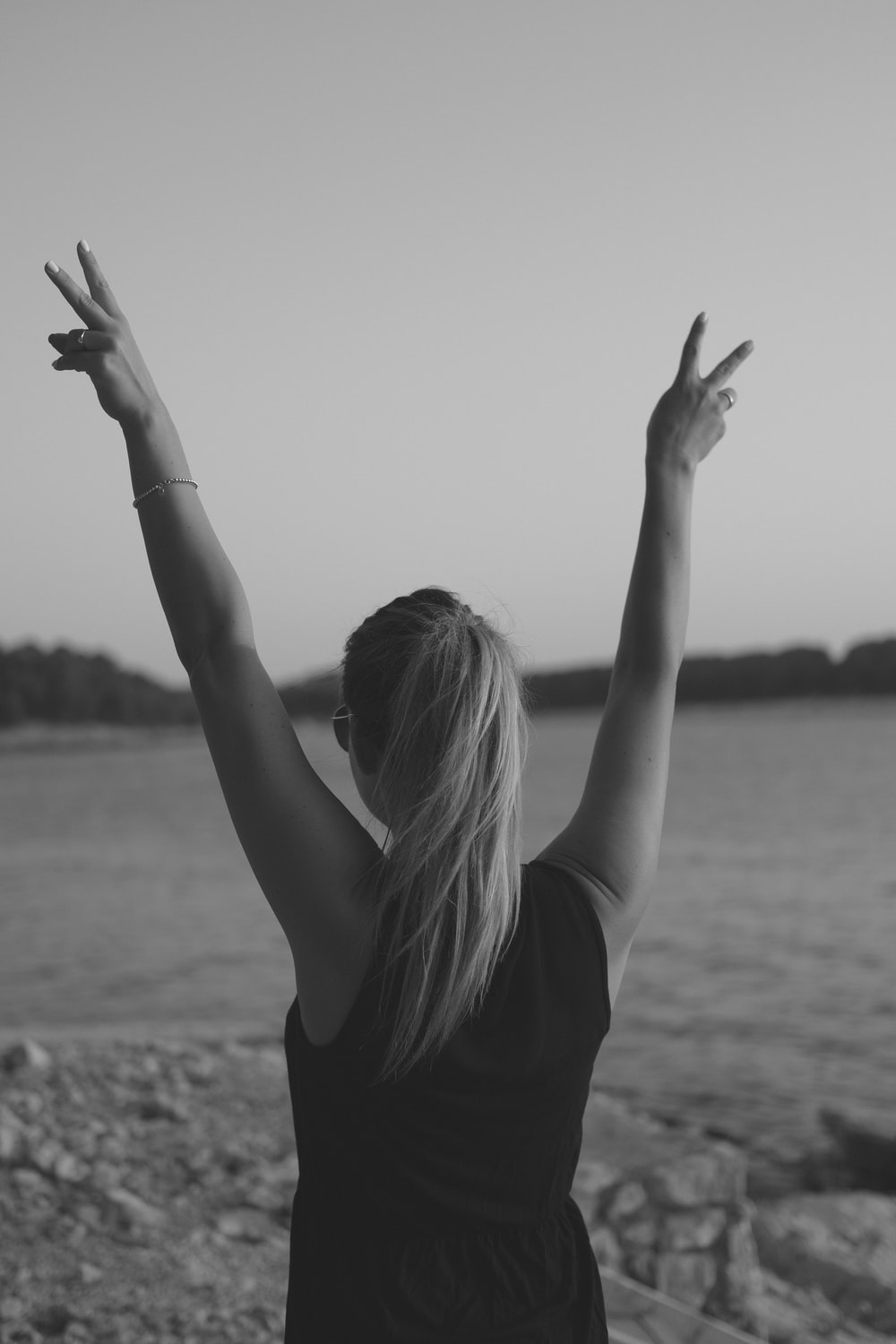 grayscale photo of woman wearing black tank top walking on seashore while doing peace hand sign
