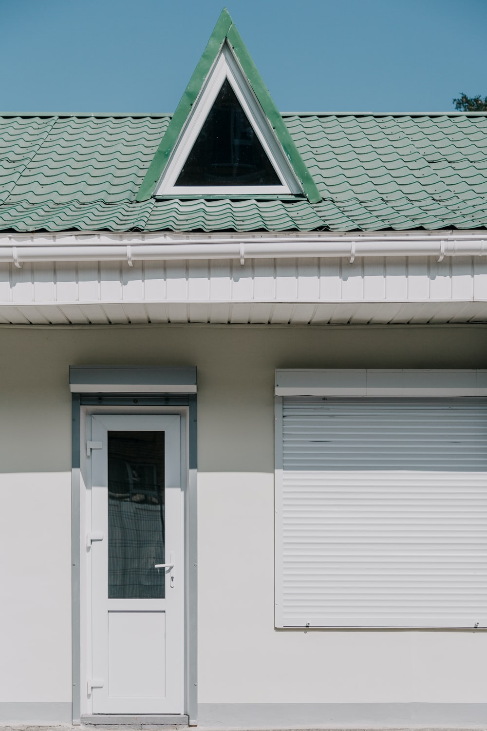 white wooden door and green house roof