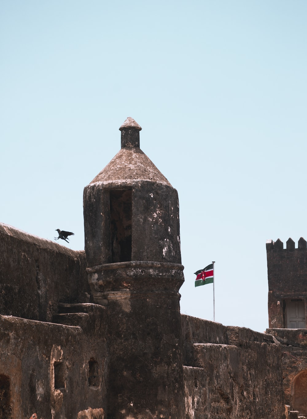 blue, red, and green flag on castle wall
