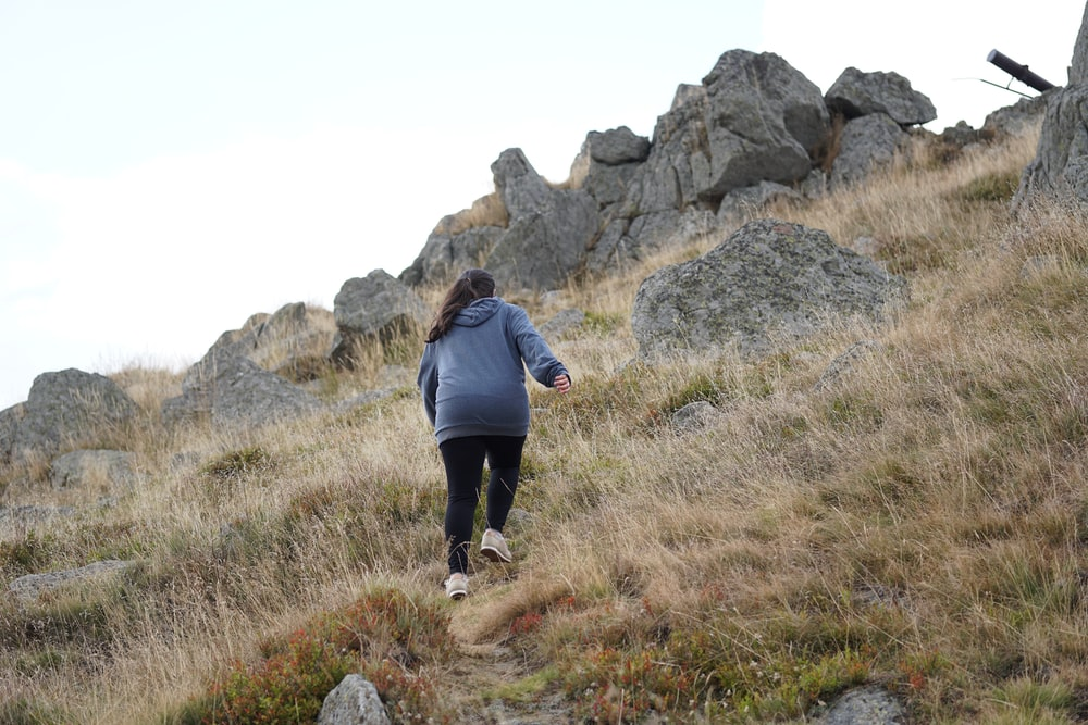 woman in gray jacket climbing a mountainside