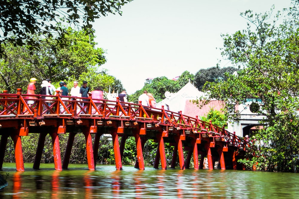 people standing on red wooden bridge during daytime