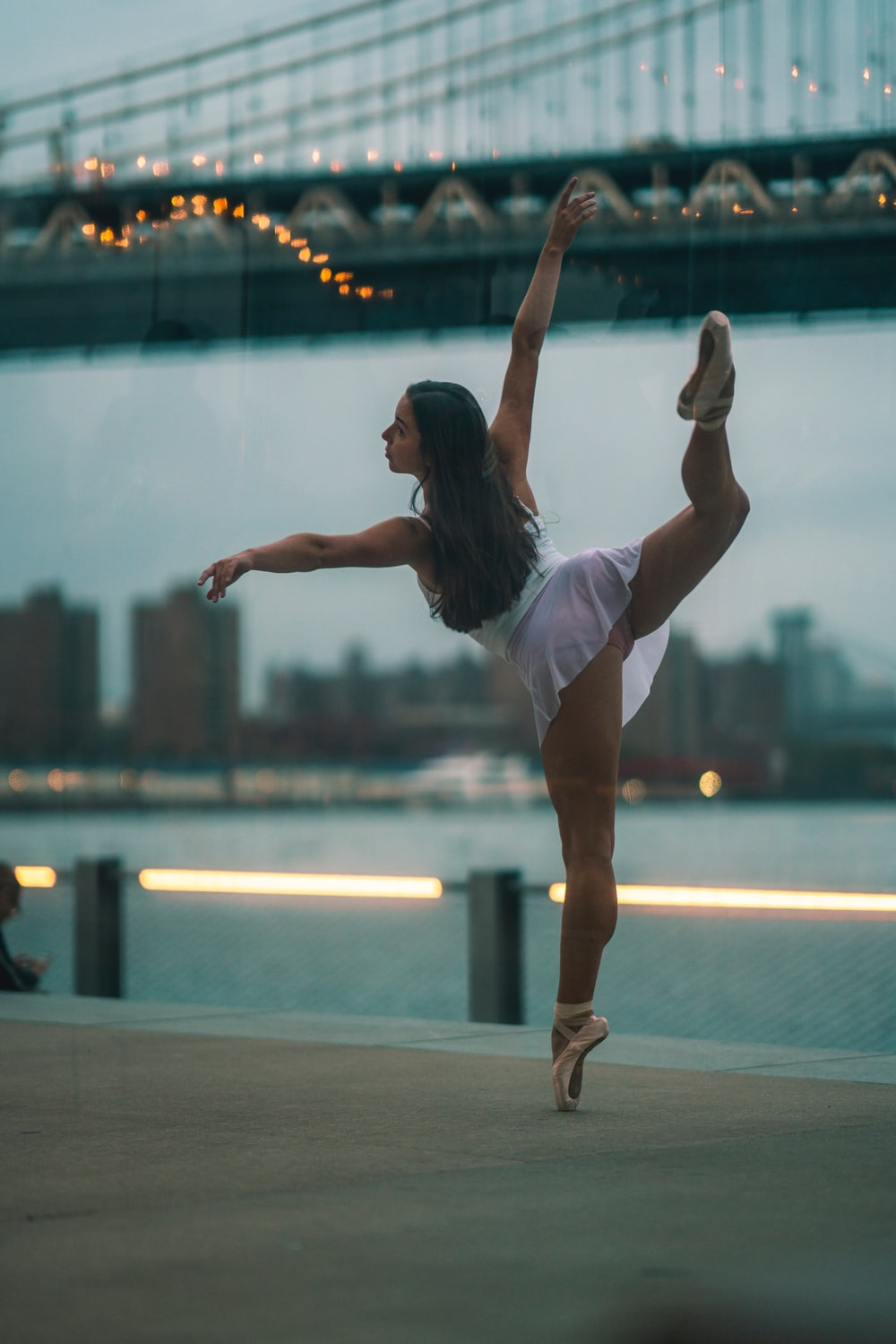 ballerina standing on one foot tiptoeing at the city bay during day