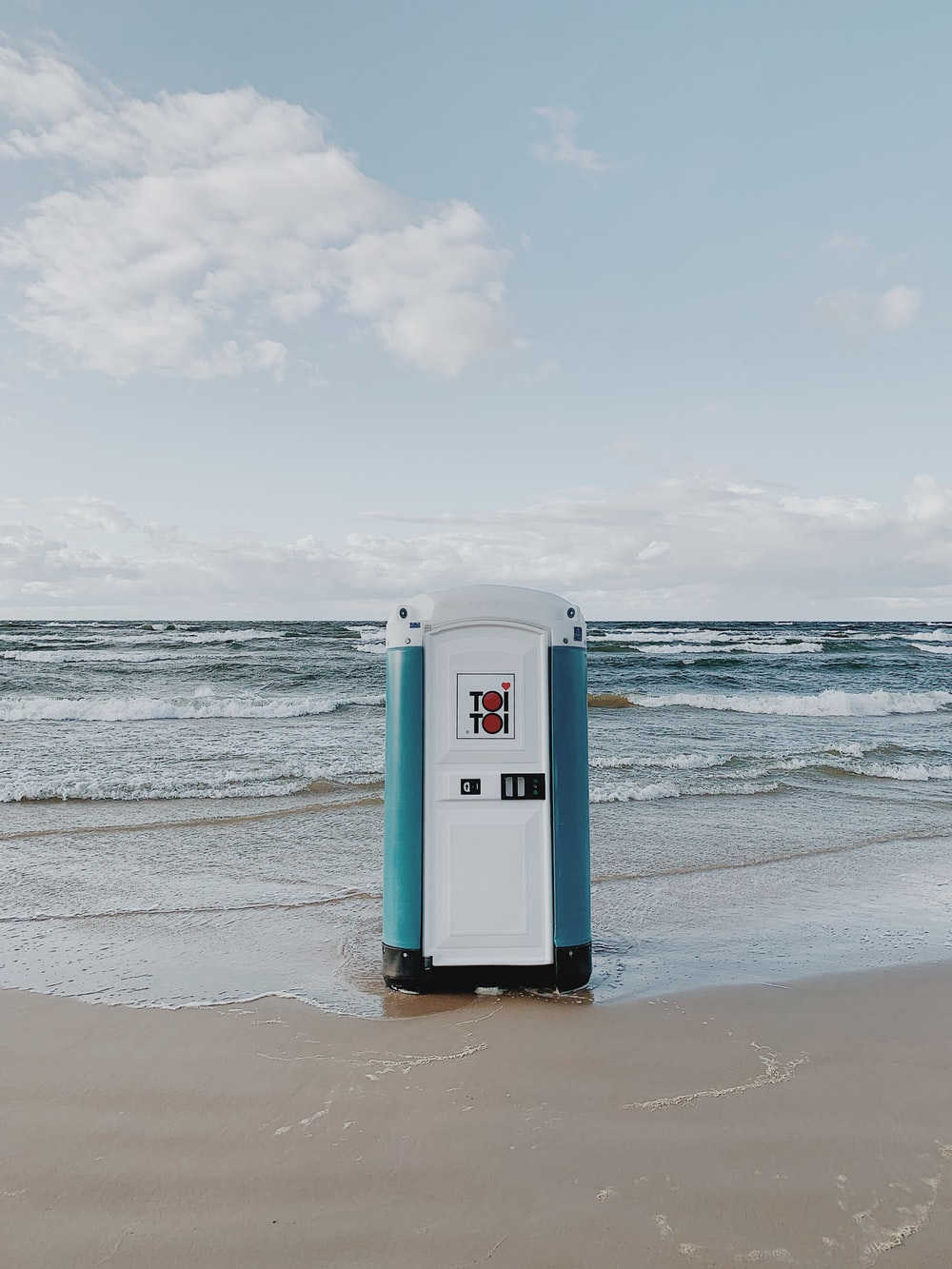 white and blue booth on seashore