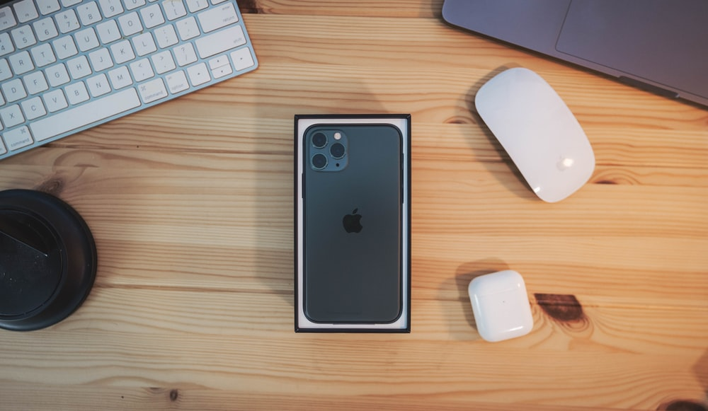 black iPhone 11 beside Magic Mouse