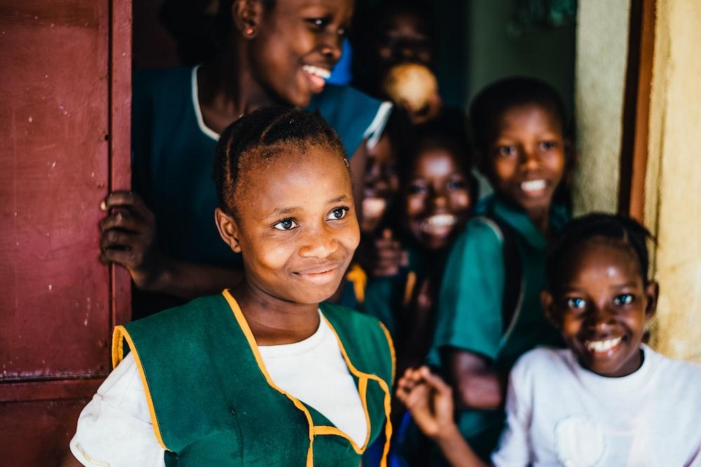 children smiling while standing near open door