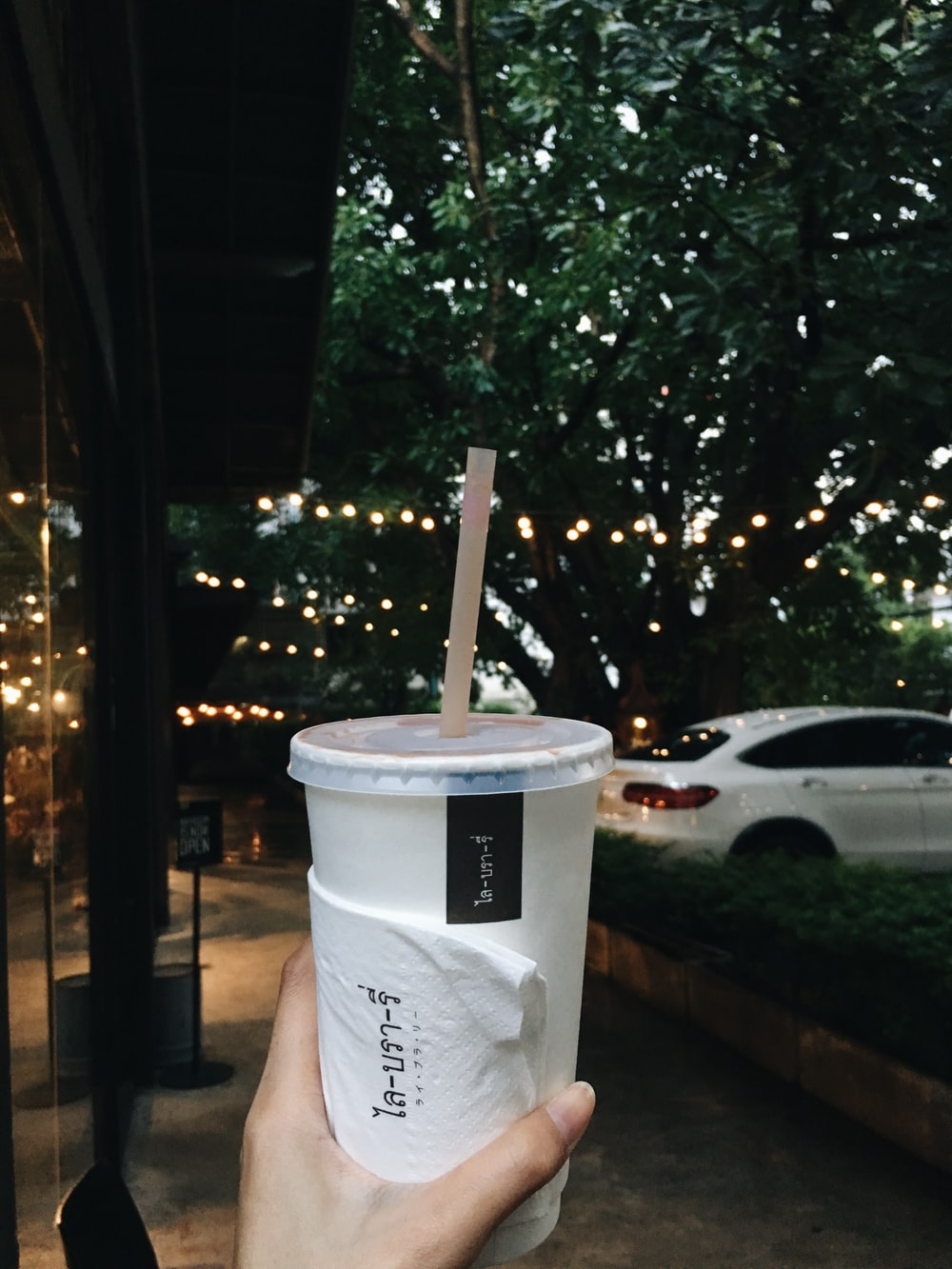 person hold a paper cup with lid and straw