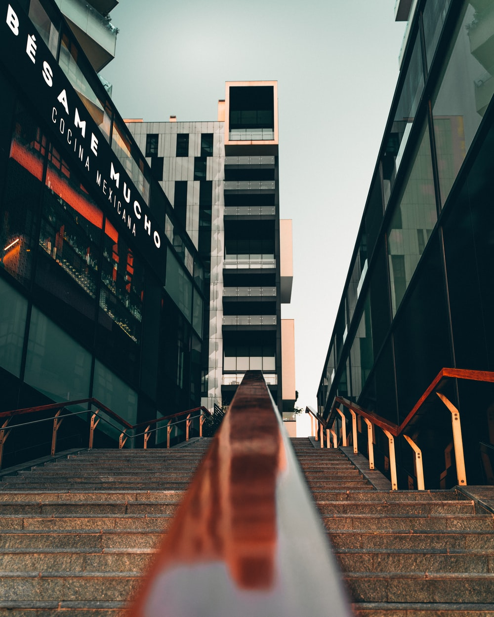 low-angle photography concrete stairs near high-rise buildings during daytime