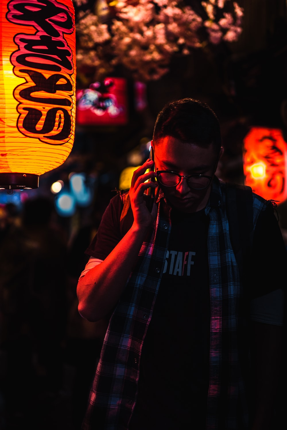 man using phone while standing during night time