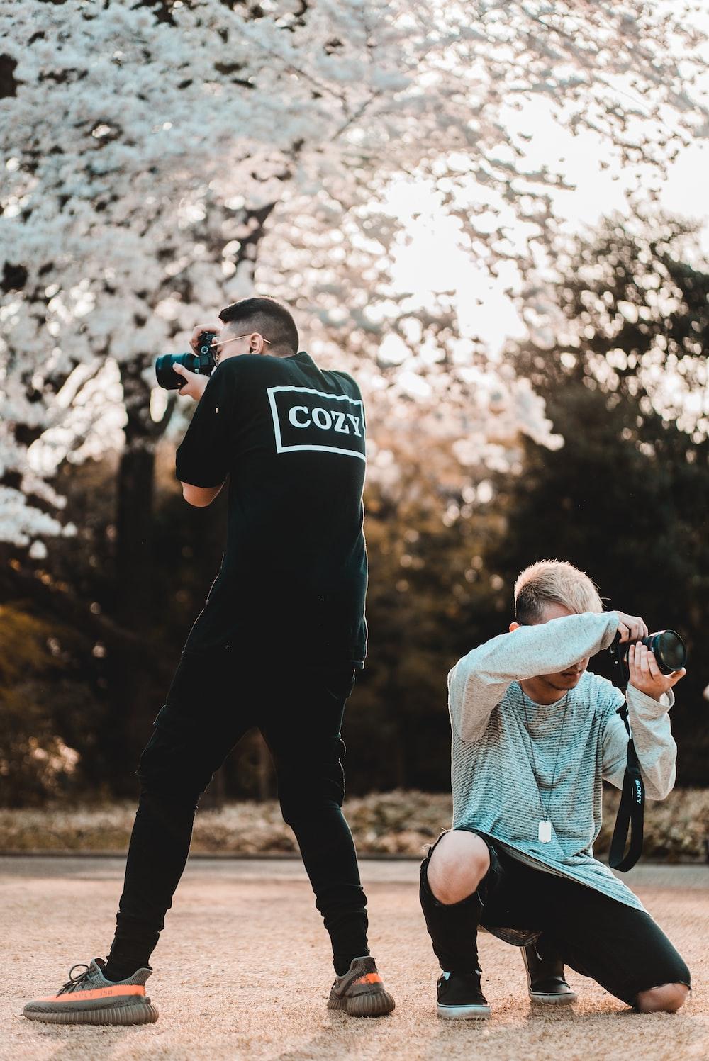 two men taking photos at daytime