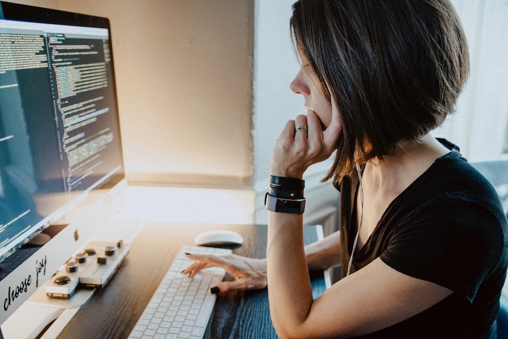 woman wearing black t-shirt holding white computer keyboard