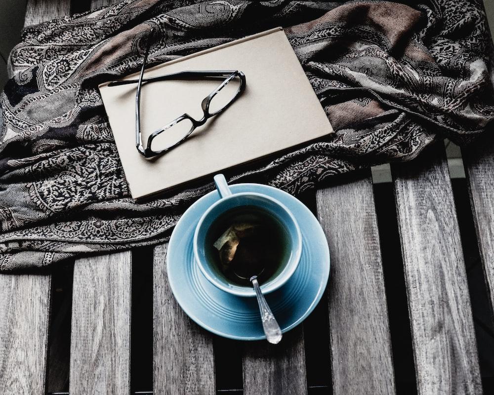 blue ceramic teacup with black liquid
