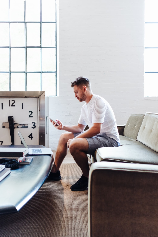 sitting man wearing white t-shirt using smartphone