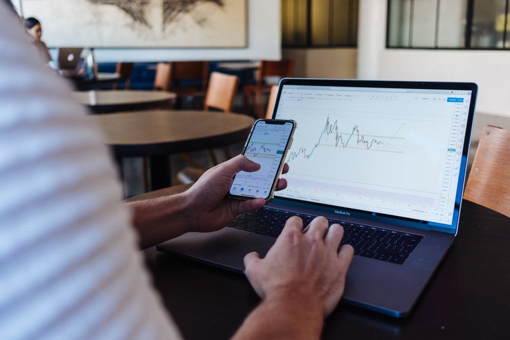 person using smartphone and MacBook Pro