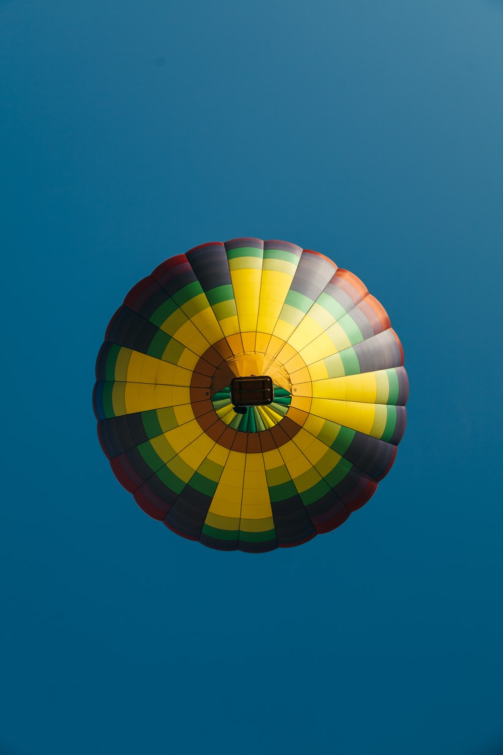 floating yellow, black, and orange hot air balloon