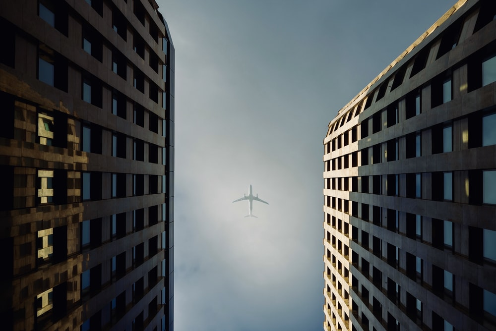 low-angle photography of high-rise buildings showing white airplane