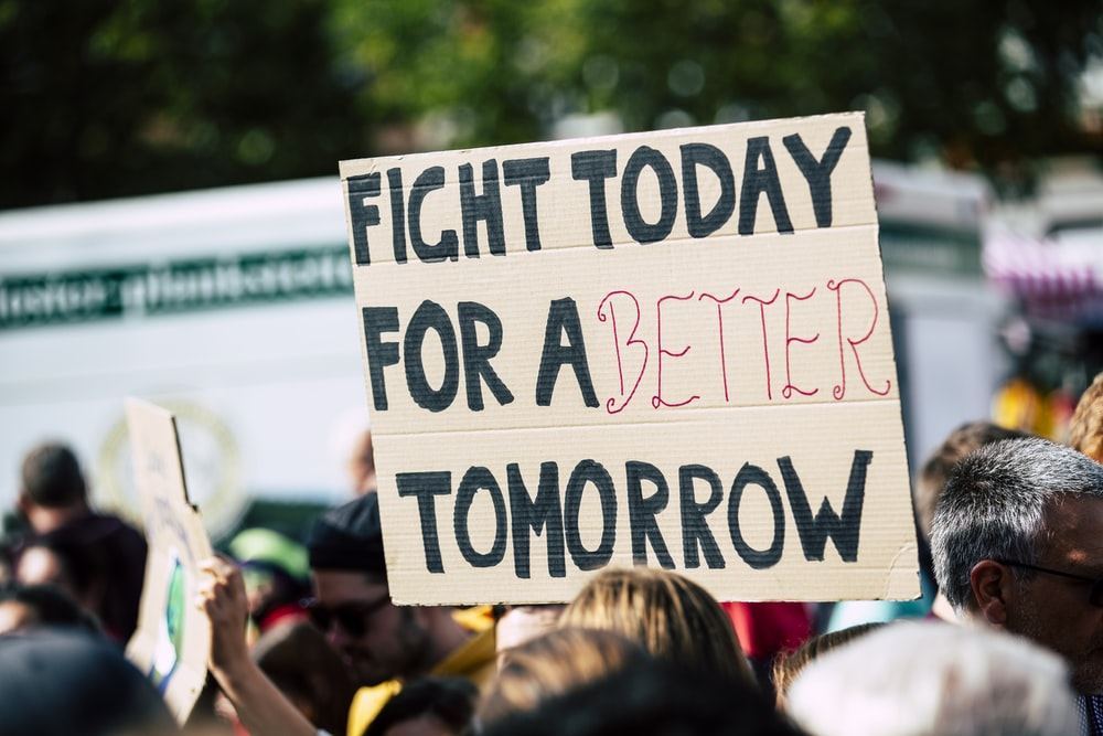 person holding fight today for a better tomorrow sign
