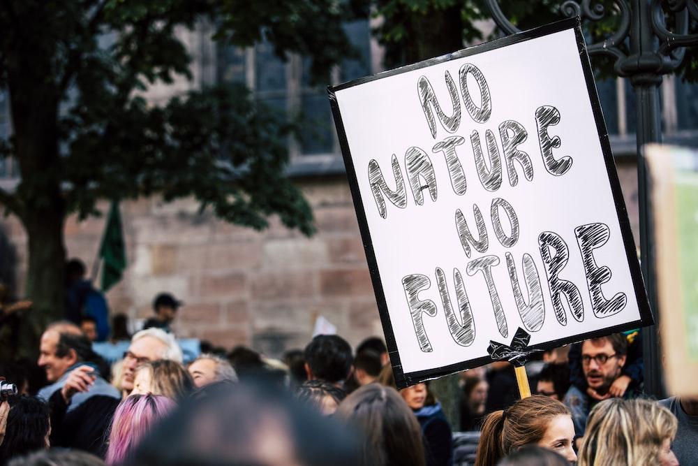 man holding No Mature No Future signage