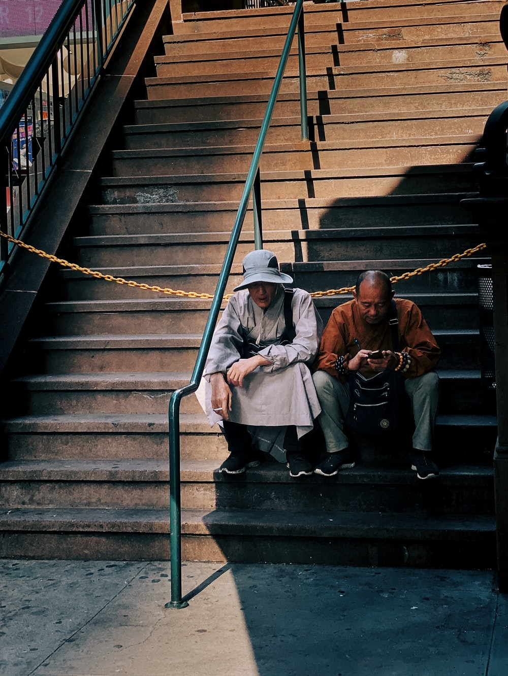 two men sitting on concrete stairs
