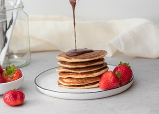 man pouring maple syrup on piled of pancake