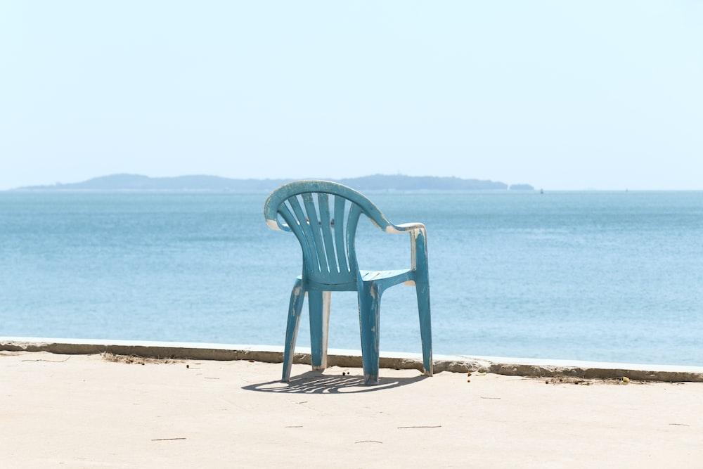 blue monobloc armchair front of sea