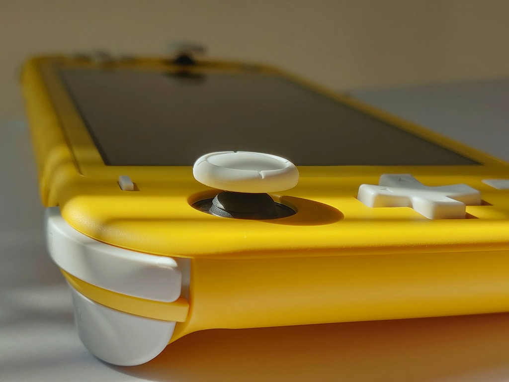 yellow and white handle game console