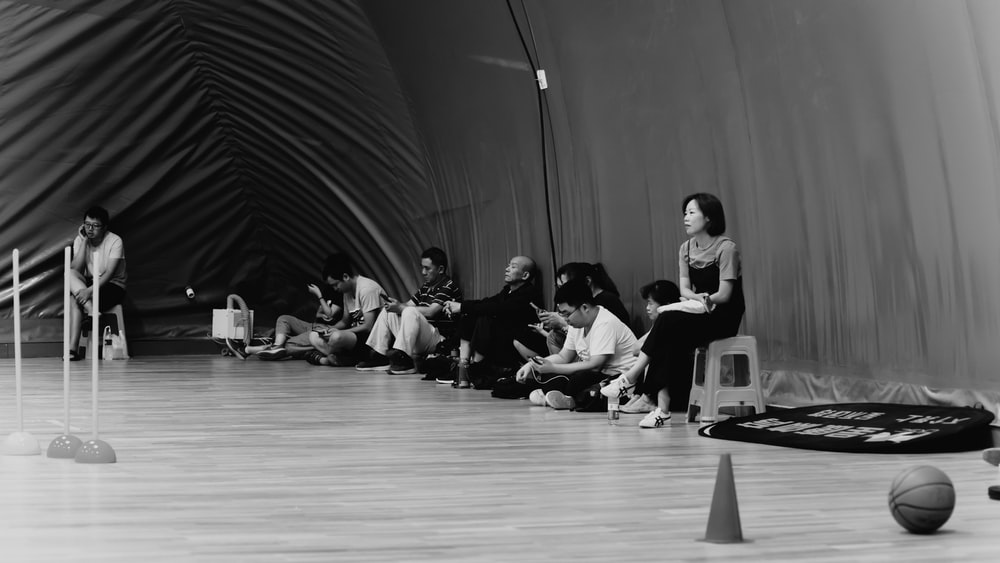 grayscale photography of people sitting inside room