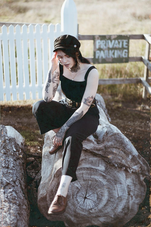 woman in black tank top sitting on tree log
